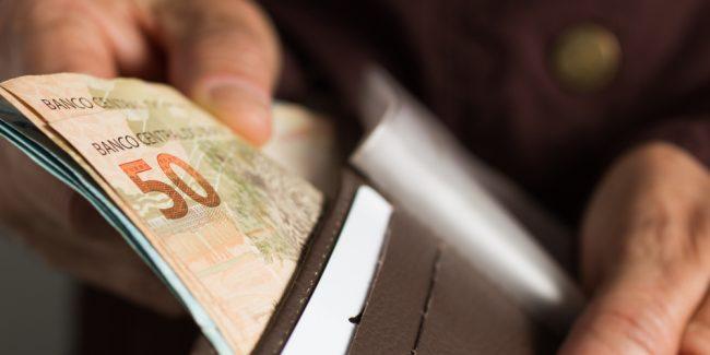 homem abre carteira com algumas cédulas de reais