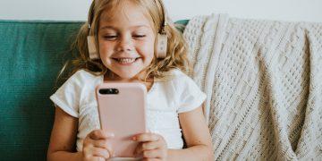 criança com celular e fone de ouvido