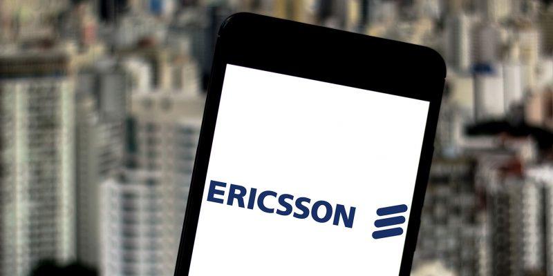 Smartphone com a logo da Ericsson e a cidade de São Paulo ao fundo.
