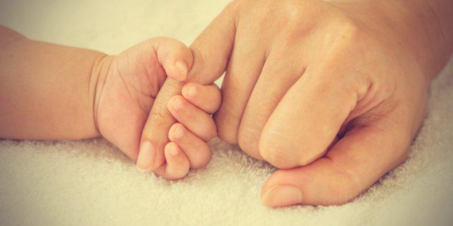 Pai segura mão de bebê recém-nascido