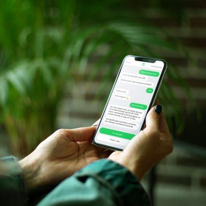 Pessoa segurando um celular com o aplicativo de Olivia na tela