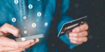 homem segura cartão e smartphone