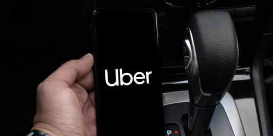Motorista segura telefone com app da Uber