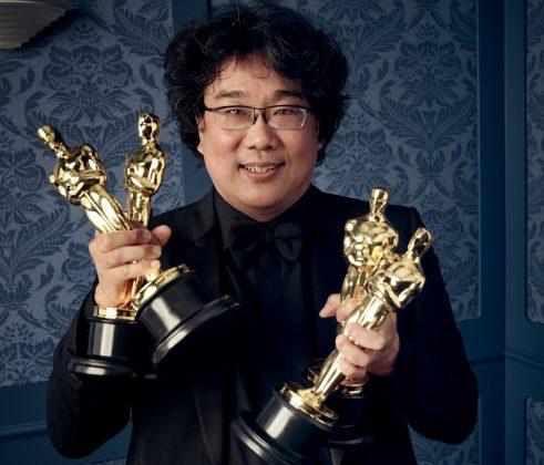 O diretor coreano Bong Joon Ho segurando 4 estatuetas do Oscar