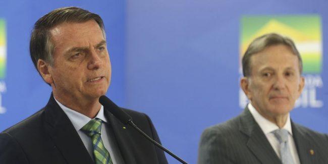 O presidente do Brasil Jair Bolsonaro (à frente), e o presidente dos Correios, general Floriano Peixoto, ao fundo