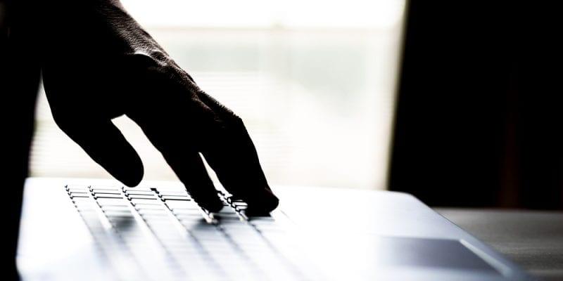a hand reaches a computer keyboard