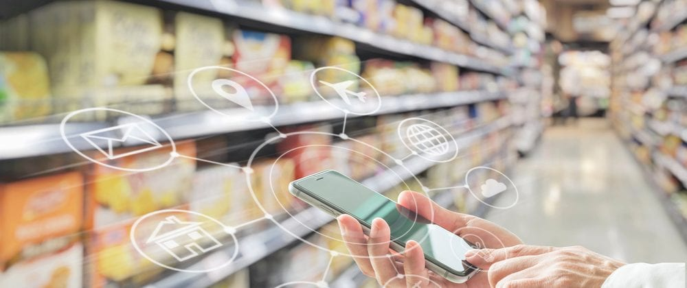 a person holds an smartphone in a supermarket