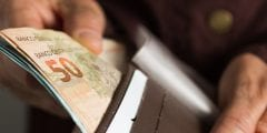 a man holds some notes of reais, the brazilian currency