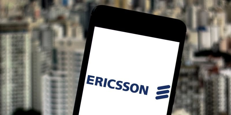 Ericsson's brand in a smartphone and the Brazilian city of Sao Paulo as background.