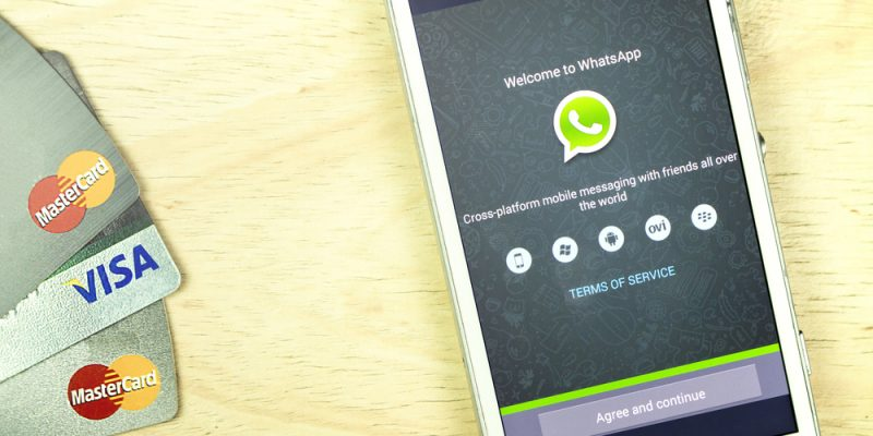 smart phone display whatsapp app and credit card on office desk