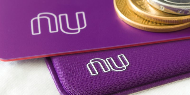 Nubank card on a white background and coins. Nubank is a Brazilian company in the segment of financial services and digital bank. largest fintech in Latin America.