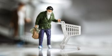 Miniature figurine wear mask business shopper pushes shopping cart on paper index with stethoscope medical.Concept internet online ecommerce mortar stores,wearing mask protective Coronavirus 2019