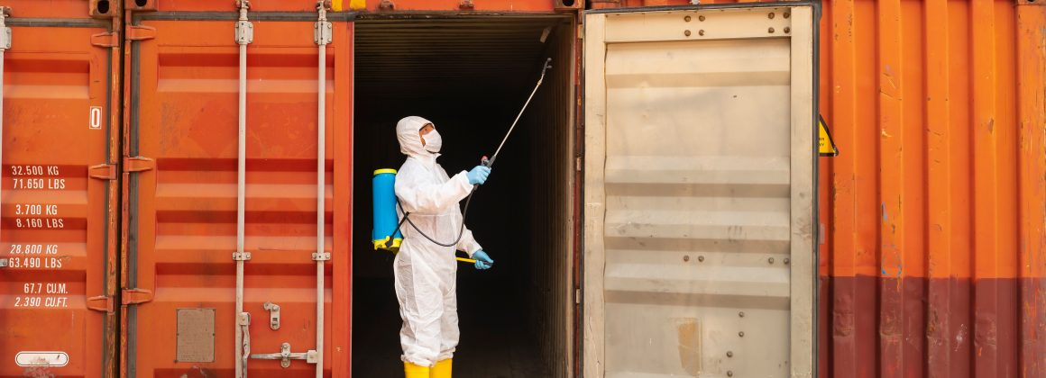 Employee wearing protective equipment chemically disinfects a container