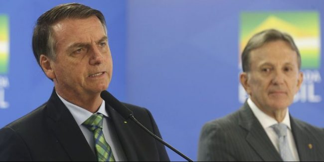 Brazilian President Jair Bolsonaro (at the front), and the President of Correios, General Floriano Peixoto, in the background.